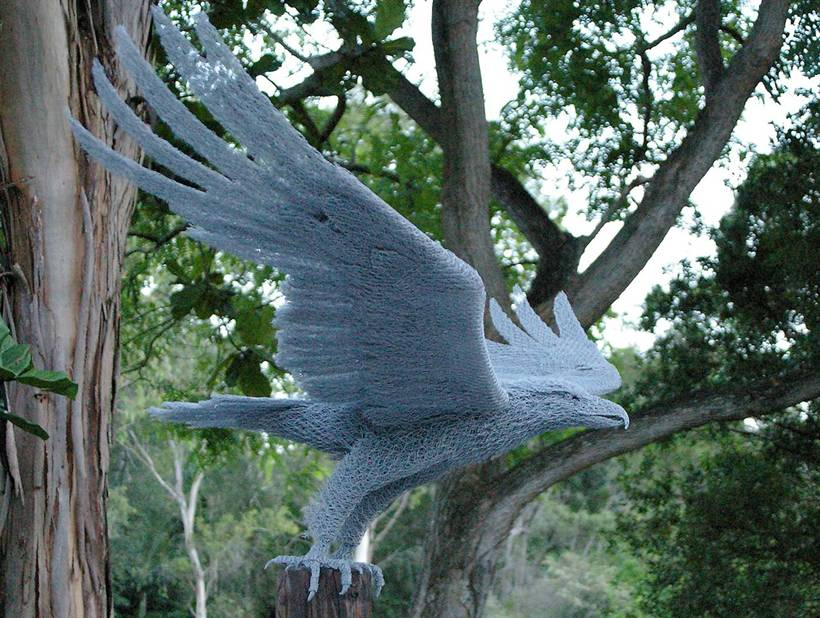An eagle sculpture falls on a tree stump spreading wings