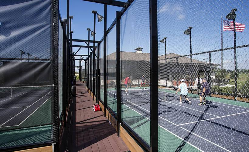 Two adjacent paddle tennis courts, one has people playing inside, and American natio<em></em>nal flag is flying.