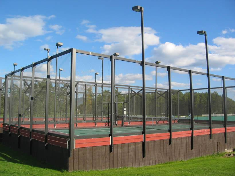 This is a huge size paddle tennis court with a high platform on ground and chicken wire mesh made fence protect it.
