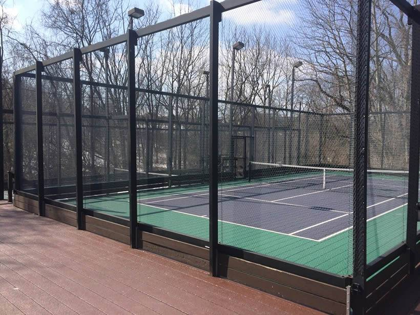 This an empty paddle tennis court in winter by day.