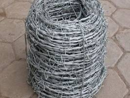 A roll of galvanized barbed wire on the ground.