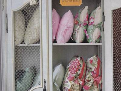 A white chicken wire french armoires has colorful bolsters inside it.