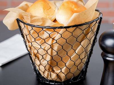Black chicken wire basket contains yellow paper and bread.