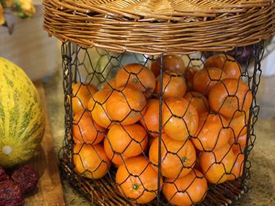 A basket, which contains oranges, is placed on table.