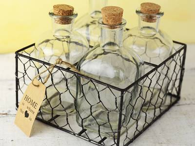 Four bottles are paced inside a chicken wire mesh made basket.