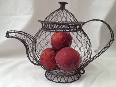 A black chicken wire mesh made teapot with three red apples in it.