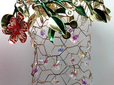 A obround chicken wire design is decorated with jewels.