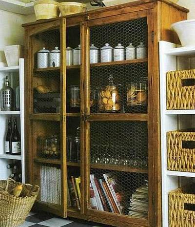 A chicken wire cupboard contains with many cookies, white cups and standing cups.
