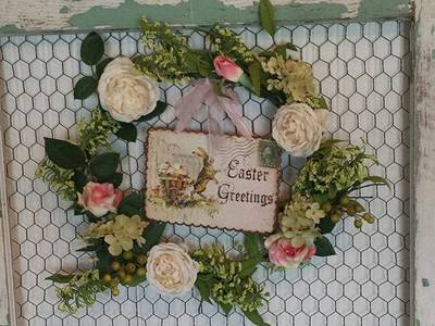 Distressed wood made chicken wire frame has a garland inside it.