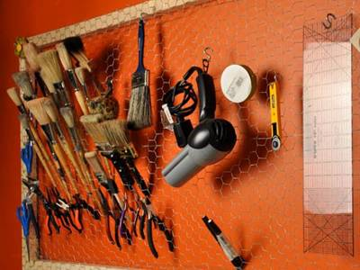 Brushes, blower and other tools are hung in a chicken wire frame on wall.