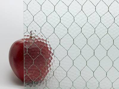 A red apple is placed behind a clear chicken wire mesh embedded glass.