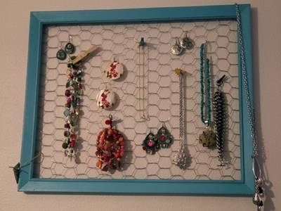 Blue chicken wire frame is hung on the wall, and necklace is hung inside the frame.