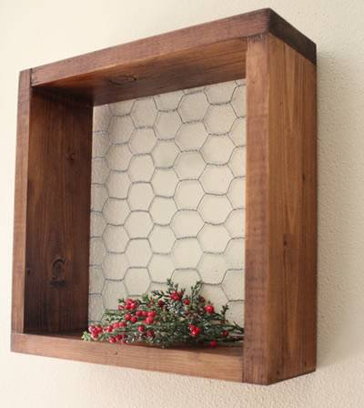 A timber and chicken wire mesh made chicken wire frame is hung on the wall, and flowers are placed on the plate.