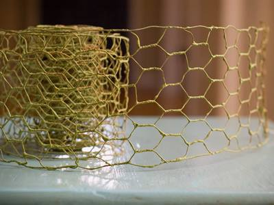 A roll of yellow chicken wire ribbon is lying there with part of ribbon extended.