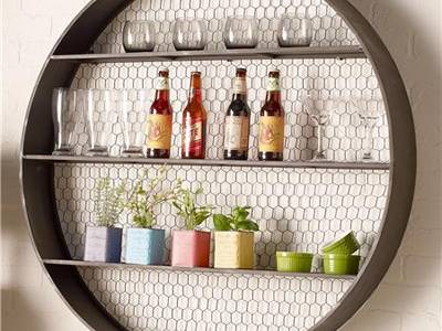 A Round Shelf Has Wine, Cups And Plants Inside.