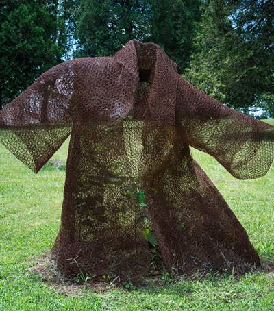 A rusty chicken wire mesh made coat is placed in a some forest like place.