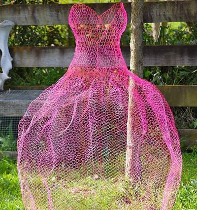 A chicken wire mesh made pink dress is place on the ground.