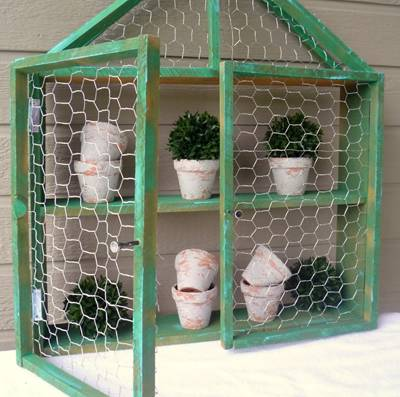 A green chicken wire shelf is mounted on wall, plants are placed inside.