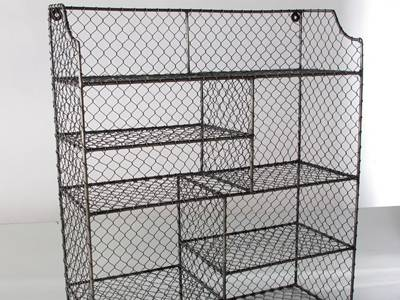 A rusty chicken wire shelf has several grids.