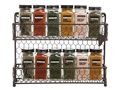 Bottle of spice are placed on a chicken wire mesh made shelf in kitchen.