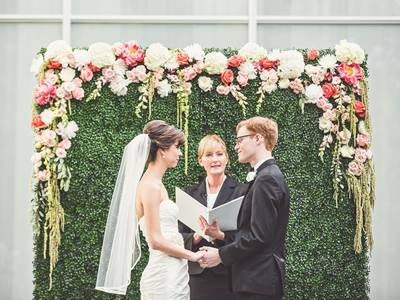 Plants and flowers are planted on a frame and the scene shows a wedding ceremony.
