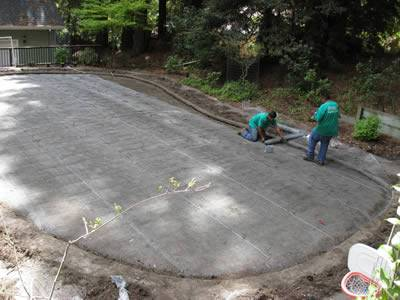 Two men are setting strips of gopher wire mesh in a oval place.