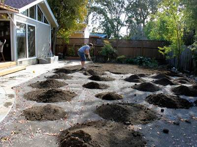 A man is flatting the soil in the front with several mounds left to deal at his back.