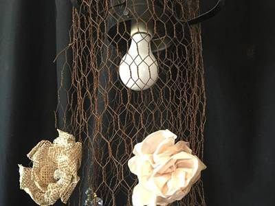 Long pendulous rustic chicken wire mesh is created as a decoration for light.