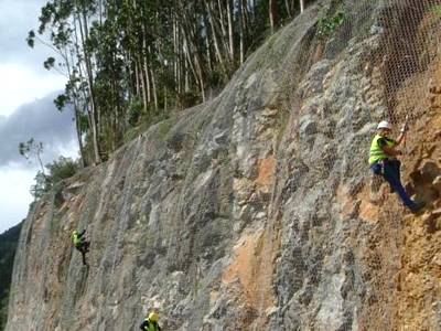 Four workers are fixing hexagonal wire netting rockfall barrier to a side of mountain near the road